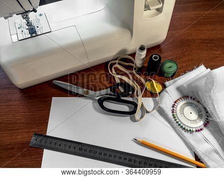 White Fabric, A Sewing Machine, Scissors, Ball Head Pins, Spools Of Thread, An Elastic Band, A Sheet