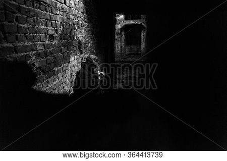 Young Man In The Coat Sitting Near The Wall In The Abandoned Buiding And Praying
