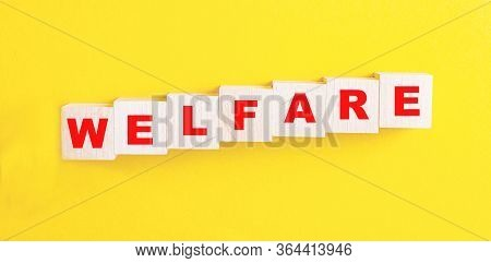 Welfare-word On Wooden Cubes On A Yellow Background Of Red Color