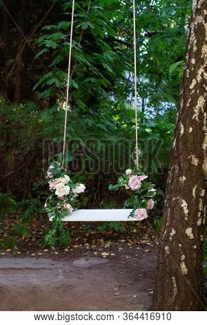 Wooden Swing In Playground Outdoors. Empty Swing Placed In Park. Wedding Swing Decorated With Flower