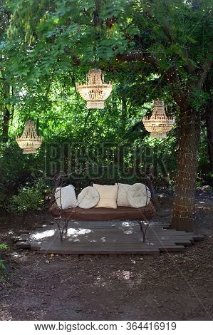 Elegant Sofa In The Garden, Outdoor Decorative Composition With Three Chandeliers. Beautiful Elegant