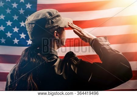 Veterans Day, Memorial Day, Independence Day.silhouette Of A Female Soldier Saluting Against The Bac