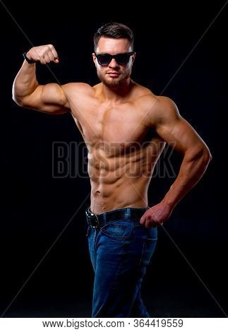 Strong Brutal Bodybuilder Man With Perfect Abs, Shoulders, Biceps, Triceps And Chest Showing His Bic