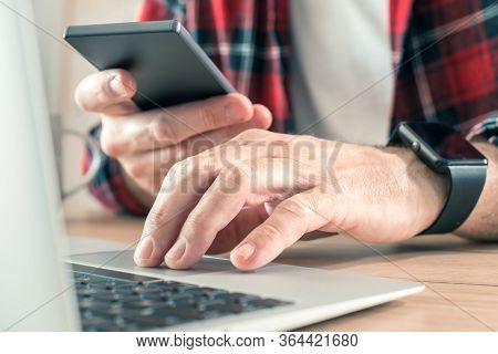 Freelancer Using Smartphone And Laptop Computer In Home Office While Telecommuting, Selective Focus