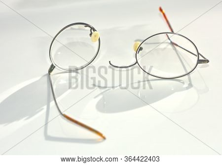 A Pair Of Titanium Wire Rim Eye Glasses That Have Broken And Split Apart On The Nose Bridge Section.