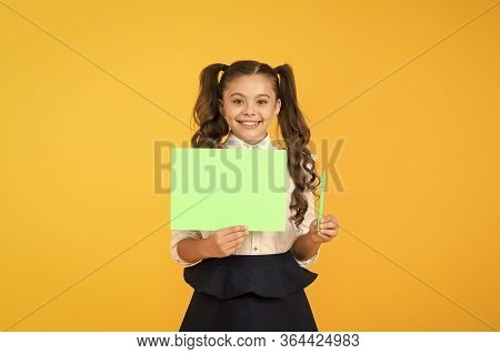 Get A Writing Pen. Little Girl Holding Blank Paper Sheet For Writing Task On Yellow Background. Smal