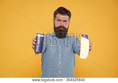 Providing Nourishing Care. Hipster Hold Hair Care Products Yellow Background. Bearded Man With Shamp