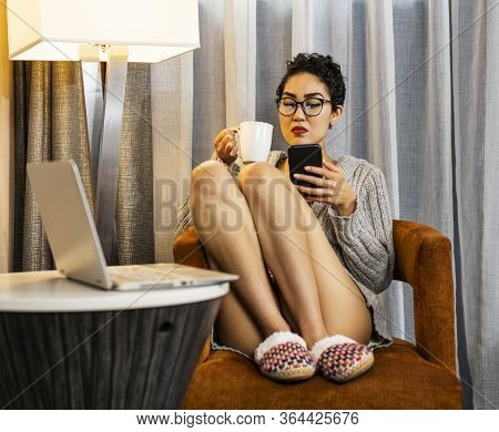 A Woman Wearing Glasses Giving Her Mobile Phone A Dirty Look
