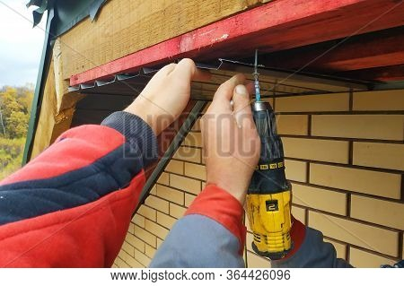 Workers Install Eaves Under The Roof Of The House.2020