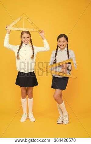 Measuring Angles At Geometry. Cute Schoolgirls Holding Triangles For Geometry Lesson On Yellow Backg