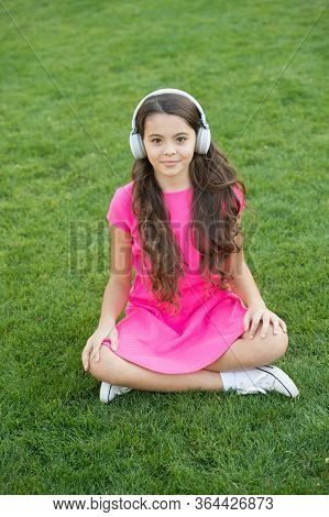 Summer Tunes. Small Girl Listen To Music On Green Grass. Little Child Wear Audio Headphones. Listeni
