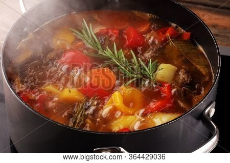 Meat Stew With Vegetables. Beef Stew With Potatoes, Carrots And Fresh Herbs On Table.