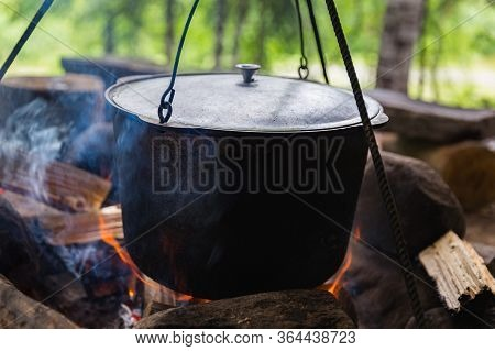 Cauldron For Cooking A Meal Outdoor Hangs Over A Bonfire. Leisure In A Camp In A Forest