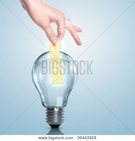 Hand putting a busines term into a light bulb