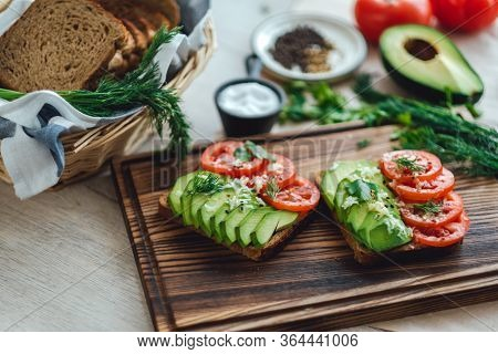 Healthy Vegan Homemade Sandwich, Avocado And Tomatoes With Dark Grain Bread On A Wooden Board.