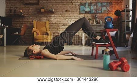 Fitness training at home. Young woman doing abdomen workout, exercising in living room. Stay at home and stay fit and healthy.