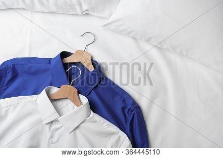 Stylish Shirts On White Fabric, Closeup. Dry-cleaning Service