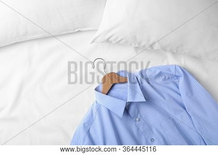 Stylish Light Blue Shirt On Bed, Space For Text. Dry-cleaning Service