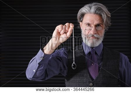 Psychotherapist With Pendulum On Black Background. Hypnotherapy Session