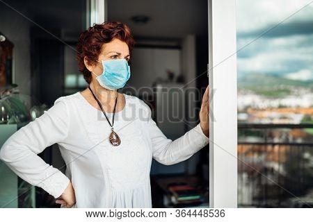 Senior Elderly Sad Woman At Home,wearing Mask On Balcony Window.coronavirus Covid-19 Disease Outbrea