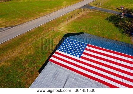 A country road with an American Flag painted on a barn near a farm in the United States