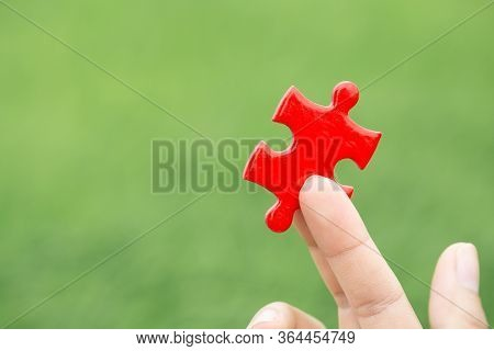 Pieces Of Red Puzzles. Businessmen Hand Holding Pieces Of Red Puzzles.business Concept For Completin