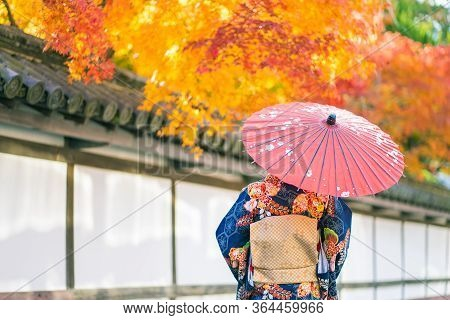 Geishas Girl Wearing Japanese Kimono Among Red Wooden Tori Gate At Fushimi Inari Shrine In Kyoto, Ki