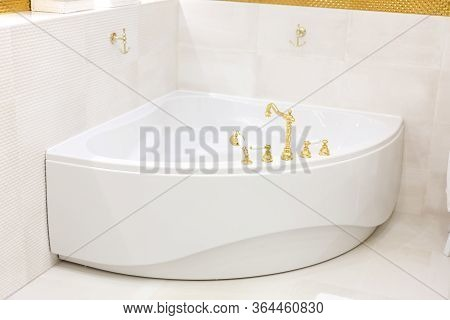 White Corner Bath, Whirlpool. Golden Faucet, Faucet On The Bathroom. Golden Hooks On The Wall. The I