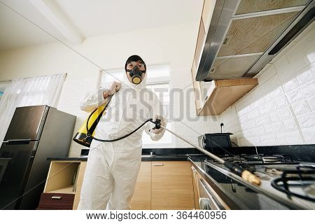 Technician In Protective Suit And Mask Spraying Chemicals In House To Prevent Spreding Pneumonia Vir
