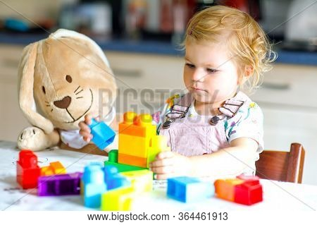 Little Toddler Girl With Plush Bunny Playing With Educational Plastic Colorful Blocs Toys. Child Hav
