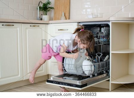 Open Dishwasher With Dirty Dishes. Little Girl Helps To Lay The Dishes. Moms Little Helper. Kitchen