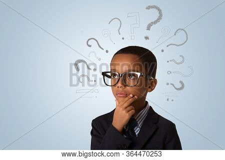 Handsome African American Little Boy Wearing Glasses And Thinking With Many Question Marks Over Blue