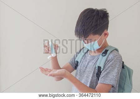 Mixed Asian Preteen Boy Wearing Mask And Applying Hand Sanitizer, School Reopen, Back To School Afte