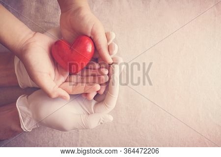 Doctor Hands With Medical Gloves Holding Child Hands And Red Heart, Health Insurance, Donation, Char