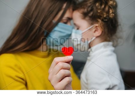 Young Mommy Hugs Cute Preschool Daughter In Protective Medical Masks Sitting On Bed, Holding Red Hea