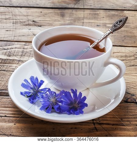 Cup With Chicory Drink And Blue Chicory Flowers On Wooden Table. Copy Space.