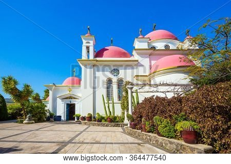 Capernaum, Lake Tiberias. Place of worship and pilgrimage. Snow-white church building with pink domes and golden crosses. Israel. The concept of religious pilgrimage and photo tourism