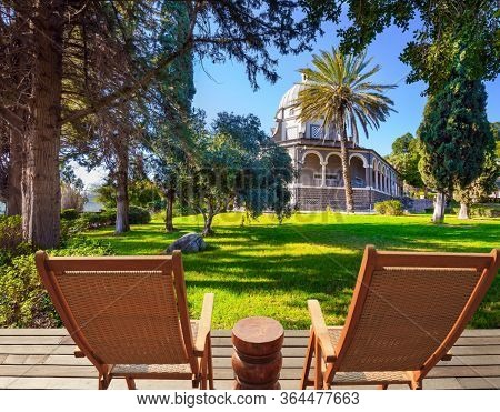Two comfortable wooden chairs - deck chairs on the platform for relaxing. Catholic Church of the Beatitudes and park around the monastery. The concept of religious pilgrimage and photo tourism