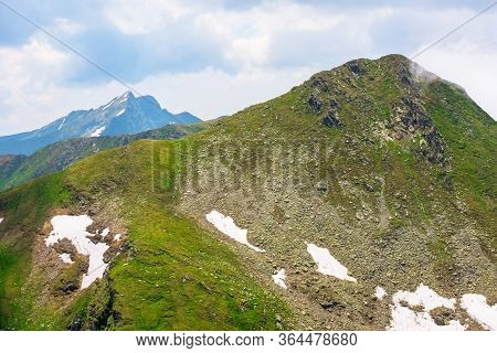 Stunning Landscape In High Mountains. Grass And Spots Of Snow On The Slopes. Rocky Peak In The Dista