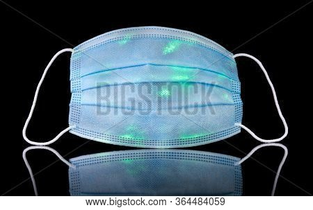 Contaminated medical face mask with glowing green spots representing germs, bacteria, or corona virus. Wear a mask to stop the spread of the coronavirus.