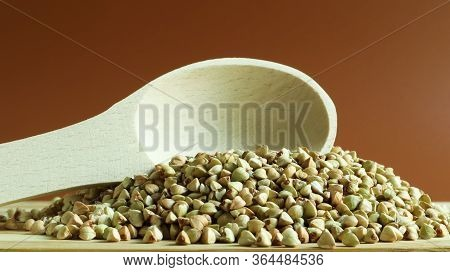Buckwheat Scattered Background, Raw Green Cereal In A Wooden Spoon. Healthy Groats. Organic Raw Non-