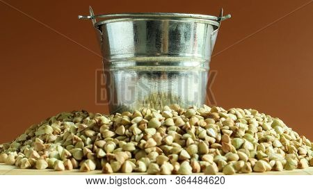 Small Metal Bucket With Raw Buckwheat On A Board On A Brown Background. Organic Vegetarian Food. The