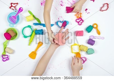 Two Little Girls Play With Modeling Clay On White Background. Top View. Child Sculpting Pink Heart F