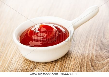 Tomato Ketchup In Small White Sauceboat With Handle On Wooden Table