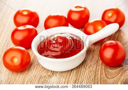 Scattered Tomato Cherry And Ketchup In Small White Sauceboat With Handle On Wooden Table