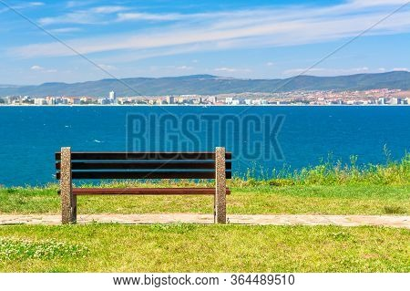 Bench On The Sunny Beach Shore. Beautiful Skyline View From Empty Park With Paved Footpath On The Se
