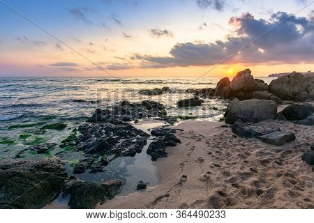 Idyllic Sunrise On The Sea Shore. Waves Crashing Rocks On Sandy Beach. Beautiful Cloudscape Above Th