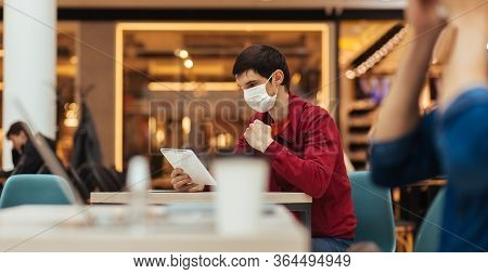 Cafe Patrons In Protective Masks Working On Their Laptops