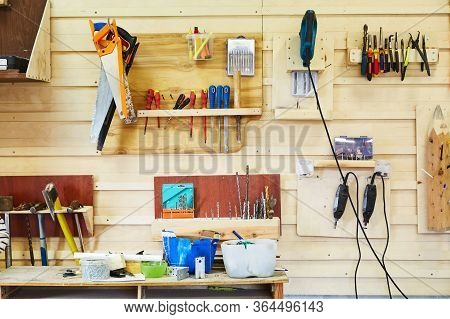 Tools Hanging On The Wall In A Carpentry Workshop. Saws, Screwdrivers, Jigsaws, Hammers, Drills, Etc