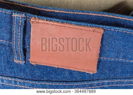 Blank Leather Label Sewed On A Waistband Of The Blue Jeans Behind, Fragment Close-up